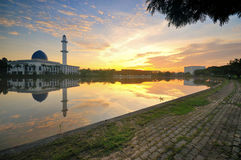 Dramatic sunset over the mosque with sky reflections on water Stock Images
