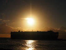 Dramatic Sunset over Pacific Ocean with Cargo Ship passing throu. Gh the water off the coast of  Oahu, Hawaii Royalty Free Stock Photo