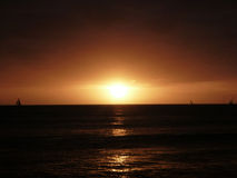 Dramatic Sunset over Pacific Ocean near Waikiki. With sail boats in the water on Oahu, Hawaii Stock Image
