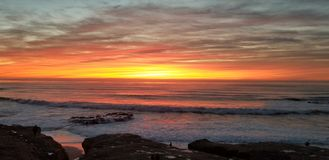 Dramatic Sunset over Pacific Ocean - Waves Crashing on the Rocks. In La Jolla California in San Diego area. Beautiful reflections on the water with surfers royalty free stock images