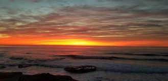 Dramatic Sunset over Pacific Ocean - Waves Crashing on the Rocks. In La Jolla California in San Diego area. Beautiful reflections on the water with surfers royalty free stock photography