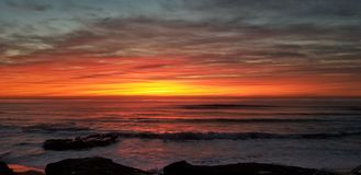 Dramatic Sunset over Pacific Ocean - Waves Crashing on the Rocks. In La Jolla California in San Diego area. Beautiful reflections on the water with surfers royalty free stock photo