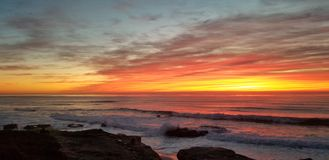 Dramatic Sunset over Pacific Ocean - Waves Crashing on the Rocks. In La Jolla California in San Diego area. Beautiful reflections on the water with surfers royalty free stock image