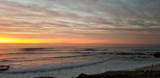 Dramatic Sunset over Pacific Ocean - Waves Crashing on the Rocks. In La Jolla California in San Diego area. Beautiful reflections on the water with surfers royalty free stock photos