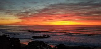 Dramatic Sunset over Pacific Ocean - Waves Crashing on the Rocks. In La Jolla California in San Diego area. Beautiful reflections on the water with surfers stock photo