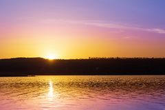 Dramatic sunset over river with orange and purple colors.Sun goes down over pond and forest silhouette. Beautiful nature backgroun. D Stock Photo