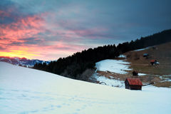Dramatic sunset over snowy mountains and huts Royalty Free Stock Photo