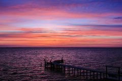 Dramatic Sunset Over the Sound. Purple and orange bands of clouds illuminate the water below with an unusual glow.  Silhouette of pier and boat dock extend into Stock Images