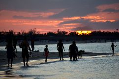 Silhouettes of people walking on the shore. Dramatic sunset over a tropical beach in the Caribbean Cayo Coco, Cuba. Silhouettes of people walking on the shore stock photography