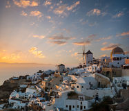 Dramatic sunset over the windmills of Oia village, Santorini Stock Photo