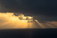 Dramatic sunset rays through a cloudy dark sky over the ocean Stock Images