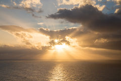 Dramatic sunset rays through a cloudy dark sky over the ocean.  royalty free stock images