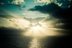 Dramatic sunset rays through a cloudy dark sky over the ocean Royalty Free Stock Image