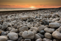 Dramatic sunset and rocks on the beach Stock Photography