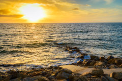 Dramatic sunset on the rocky beach Stock Images