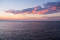 Dramatic sunset seascape with purple cloud floating above the calm sea royalty free stock images