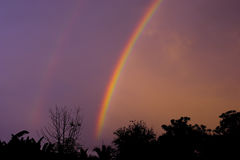 Dramatic sunset sky with double rainbow over countryside landsca Royalty Free Stock Photography