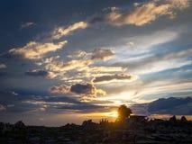 Dramatic sunset sky over rocks. Rock cairn. stock image