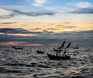 Dramatic sunset sky on the sea with fishing boat Stock Image