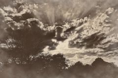 Dramatic sunset sunrise rays of light clouds sepia retro vintage Royalty Free Stock Image