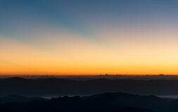 Dramatic twilight sunset and sunrise sky over mountain and fog. Stock Image