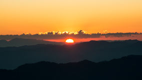Dramatic twilight sunset and sunrise sky over mountain layer. Stock Image