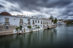 A dramatic urban landscape of ancient houses on river. Tavira, Portugal. Stock Image