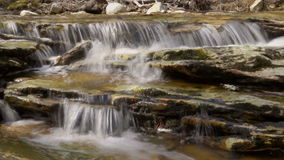 Dramatic view as water pours over the rocks of a creek. Blurred motion dramatic view as water pours over the rocks of a creek stock video footage