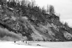Dramatic view of bluffs overlooking calm winter coastline, peopl Royalty Free Stock Photo