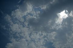 DRAMATIC VIEW OF CLOUDS IN SKY. Sun peering brightly through dark clouds in a moody ominous sky in the day royalty free stock photography