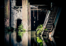 Dramatic view of damaged and abandoned building. Dramatic view of damaged escalators in abandoned shopping mall sunken by rain flood waters. Apocalyptic and evil Royalty Free Stock Images