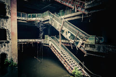 Dramatic view of damaged and abandoned building. Dramatic view of damaged escalators in abandoned shopping mall sunken by rain flood waters. Apocalyptic and evil Stock Images