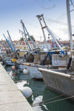 Dramatic view on fishing boats and ships in the harbor Royalty Free Stock Photo