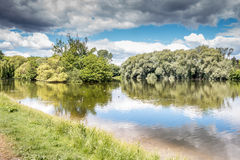 Dramatic view of a lake with green trees, blue sky and clouds. In Berlin, Germany Royalty Free Stock Image