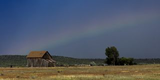 Dramatic view of  rainbow over a western barn near Norwood Color. September 14, 2017 - Dramatic view of  rainbow over a western barn near Norwood Colorado in the Stock Images