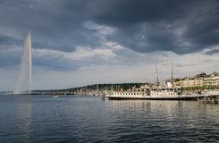 Dramatic view on touristic boat at Geneva Lake on Jet d\'Eau fountain background. Sunset time. Switzerland. GENEVA, SWITZERLAND - JUNE 15, 2013: Dramatic view on royalty free stock photo