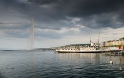 Dramatic view on touristic boat at Geneva Lake on Jet d\'Eau fountain background. Sunset time. Switzerland. GENEVA, SWITZERLAND - JUNE 15, 2013: Dramatic view on stock images