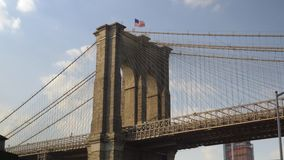 Dramatic View Under Brooklyn Bridge. 8713 A dramatic low angle view from under the Brooklyn Bridge on a summer day stock video footage