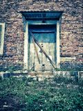 Dramatic vintage photo of an old abandoned mansion. House with the ghosts. Locked door with padlock stock photo