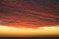 Dramatic Volcanic Crimson Sunset over Pacific Ocean stock photos