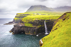 Dramatic waterfall on Faroe Islands and the village Gasadalur Stock Photos