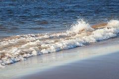 Dramatic wave crashing on the shoreline, with wind blown spray. Water splashing background. Wave crashing on the beach.  stock images