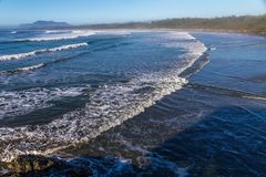 Dramatic waves sweep over Long Beach, Tofino, BC. Gentle waves breaking over Long Beach just after  sunrise during high tide.  Mist from the ocean hangs in the Stock Images