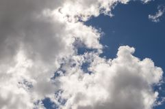 Dramatic white billowy clouds brightly back lit, blue sky. Royalty Free Stock Photos