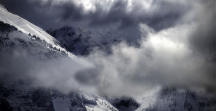Dramatic Winter Clouds and Crystalline Alpine Snow in Colorado. Energetic winter clouds swirl around a stunning Rocky Mountains landscape in dramatic shadow and Royalty Free Stock Photo