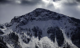 Dramatic Winter Clouds and Crystalline Alpine Snow on Mountain Peak, Colorado. The winter sun casts heavy shadows on the dramatic, tree-flanked crags of the Stock Images
