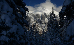 Dramatic Winter Clouds, Crystalline Alpine Snow in Rocky Mountains, Colorado. The winter sun casts heavy shadows on the dramatic, tree-flanked crags of the Rocky Royalty Free Stock Images