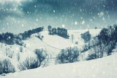 Dramatic winter landscape, mountain slope during blizzard. Holiday background, vintage image stock image