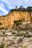 Dramatic yellow sandstone cliff against cloudy sky Royalty Free Stock Photo