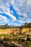 Dramatic yellow sandstone cliff against cloudy sky Stock Photography